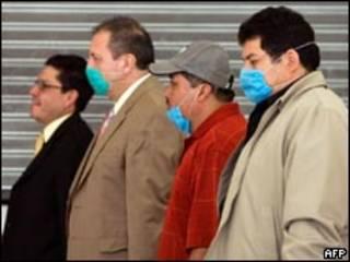 Homens usam máscaras contra gripe no Aeroporto Internacional da Cidade do México (AFP, 5/5)