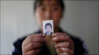 Một người mẹ cầm ảnh con trai thiệt mạng vì động đất