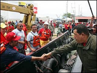 Presidente Hugo Chávez le da la mano a un empleado.