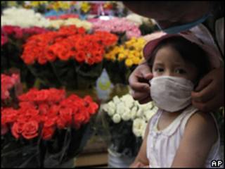 Menina usa máscara em mercado de flores na Cidade do México (AP, 8/5)