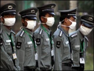 guardas de segurança chineses usam máscaras (Foto: AP)
