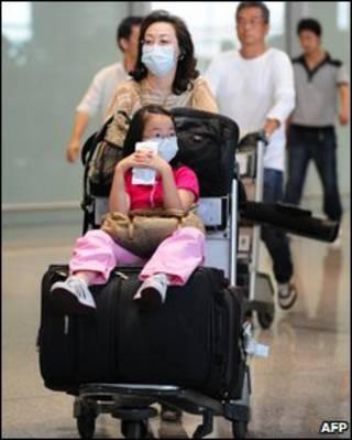 Du khách đeo khẩu trang khi hạ cánh xuống sân bay Bắc Kinh hôm 7 tháng 5, 2009