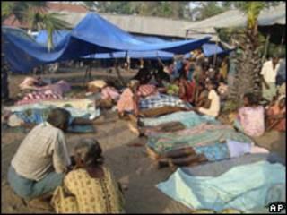 Mujeres de origen tamil junto a los cuerpos de sus familiares fallecidos