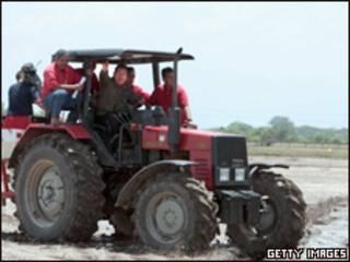 O presidente da Venezuela, Hugo Chávez, dirige um trator ao anunciar a expropriação de terras