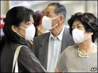 Passageiros com máscaras em estação de trem em Tóquio