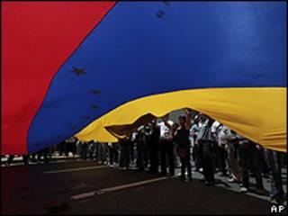 Estudiantes universitarios en Caracas ondean bandera durante manifestación