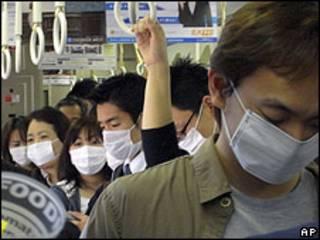 Passageiros de trem usam máscaras em Kobe