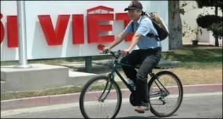 Hoàng Mai Đạt chạy xe đạp trước cửa báo Người Việt, hình Đỗ Dzũng