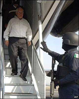 Uno de los funcionarios detenidos en el estado de Michoacán baja de avión de la policía
