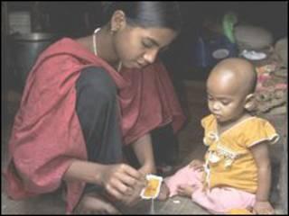 دختر بنگلادشی بچه کوچکتر را تغذیه می کند