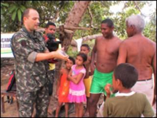 O major Carlo Endrigo Bueno Nunes faz demonstração sobre uso de preservativos a moradores da localidade de Santa Rosa, no Maranhão (foto: Alessandra Corrêa)