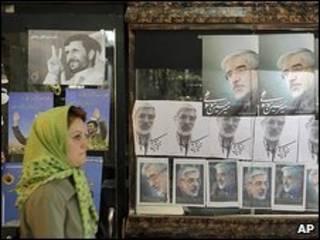 Iraniana passa por pôsteres com fotos de políticos locais