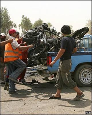 Hombre recoge motocicletas dañadas tras el atentado.