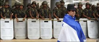 Manifestante frente a soldados hondureños