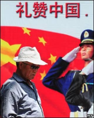 Un hombre chino pasa al frente de una propaganda del gobierno de China.