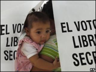 Una votante con una niña, en centro electoral en Hermosillo