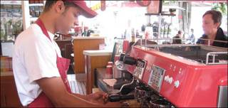 Joven sirve café en Colombia