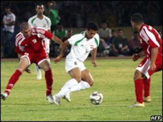 Salih Sadeer (centro), de la selección iraquí, entre dos jugadores palestinos