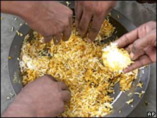 Manos recogiendo arroz para comer