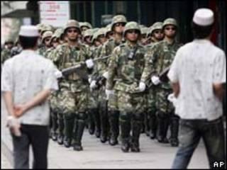 Soldados do Exército chinês fazem patrulha na cidade de Urumqi nesta segunda-feira (AP, 13/7)
