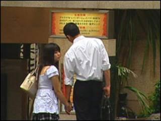 Casal japonês em frente a um dos hotéis