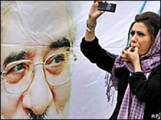Una mujer se toma una foto junto a un cartel de Hossein Mousavi