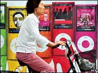 Un ciclista pasa al frente de una tienda de Apple