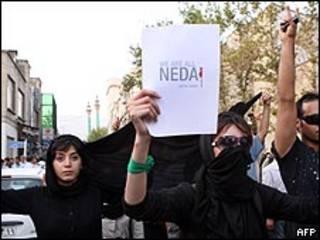 إيرانية ترفع لافتة تقول كلنا ندا خلال احتجاج في طهران