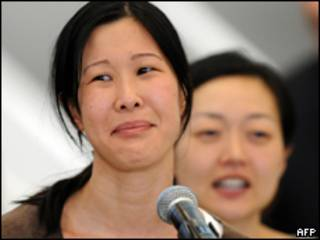 Lura Ling e Euna Lee (ao fundo) durante desembarque nos EUA (AFP)