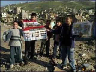 أطفال يحملون ملصقات وزعتها اليونيسيف للتحذير من القنابل