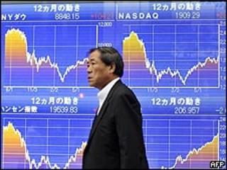 Japonés pasea junto a pantallas con datos bursátiles. Archivo.