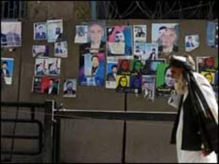 أفغاني بجوار ملصقات دعاية انتخابية