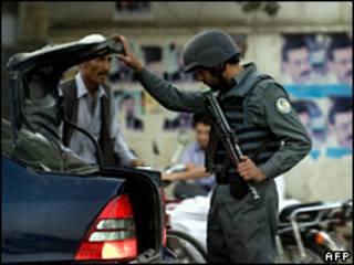 Сотрудник государственных сил безопасности Афганистана досматривает машину