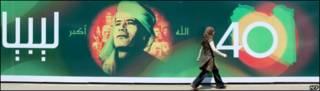 Mujer pasa frente a valla conmemorativa en Libia