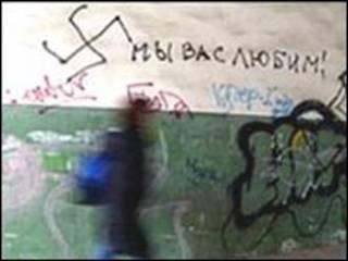 فتاة افريقية تمر جوار حائط عليه شعارات عنصرية