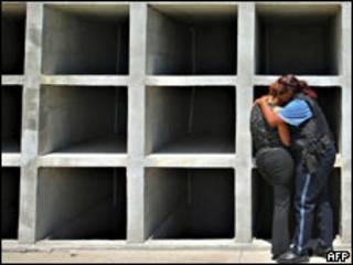 Dos mujeres policías lloran frente a tumbas vacías luego del sepelio de una compañera asesinada