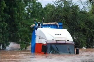 Conductor pide ayuda desde el techo de su camión.