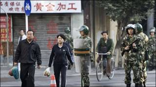 Người dân Tân Cương đi ngang qua cảnh sát