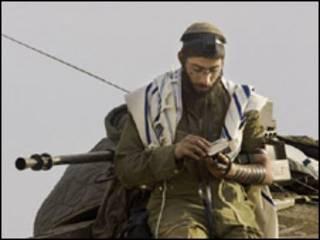 جندي اسرائيلي يصلي فوق دبابته