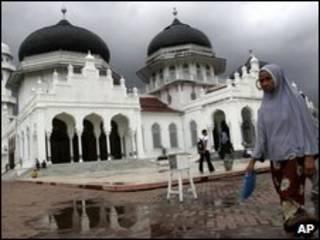 Một phụ nữ đi qua đền thờ Hồi giáo ở Aceh