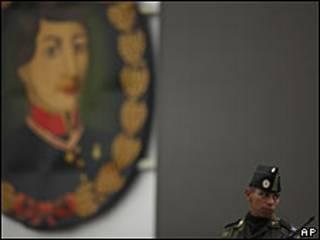 Un soldado parado próximo a una imagen del héroe mexicano Augustín Melgar.