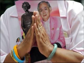 Một phụ nữ Thái Lan mang theo chân dung của Vua Bhumibol Adulyadej khi cầu nguyện cho Vua
