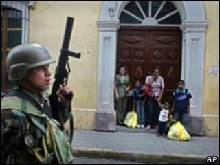 Soldado é observado por hondurenhos em rua de Tegucigalpa na última quarta-feira (AP)