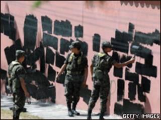 Soldados hondurenhos apagam pichação em muro perto da embaixada brasileira em Tegucigalpa