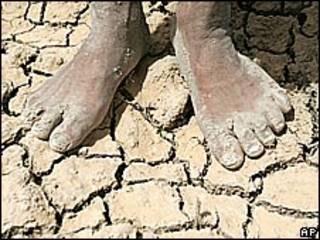 Imagen de archivo de pies descalzos sobre suelo agrietado