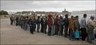 Inmigrantes en Calais, Francia, esperan por la comida de una organización benéfica