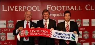 Representantes del Liverpool y Standard Chartered tras la firma del acuerdo