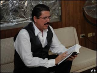 O presidente deposto de Honduras, Manuel Zelaya, lê a Bíblia na embaixada brasileira (AP, 7 de outubro)