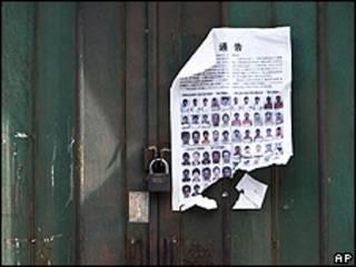 Un cartel muestra las fotos de los requeridos por la violencia de julio