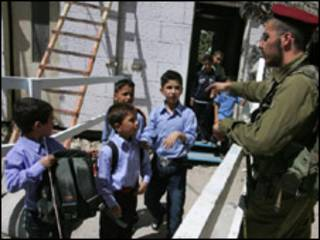 جندي اسرائيلي يوقف تلاميذ فلسطينيين لتفتيش حقائبهم